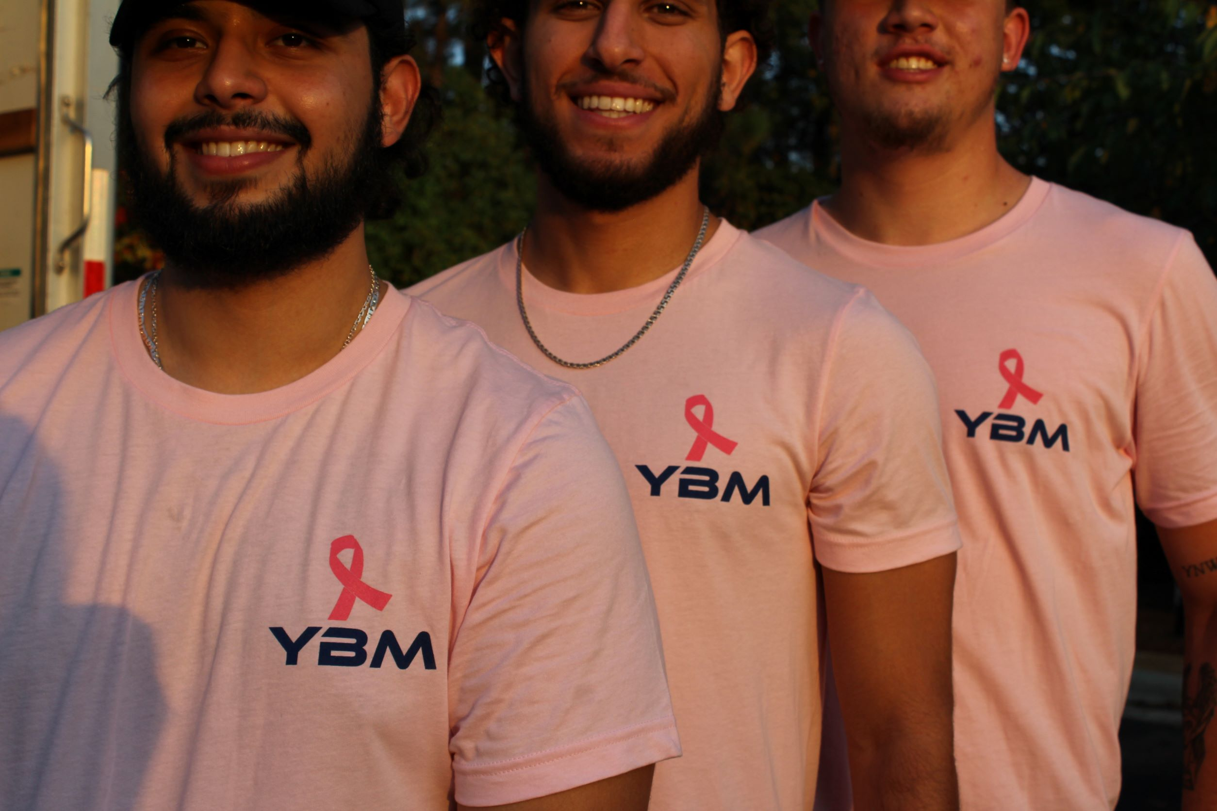 YBM crew leaders showing the breast cancer awareness merch