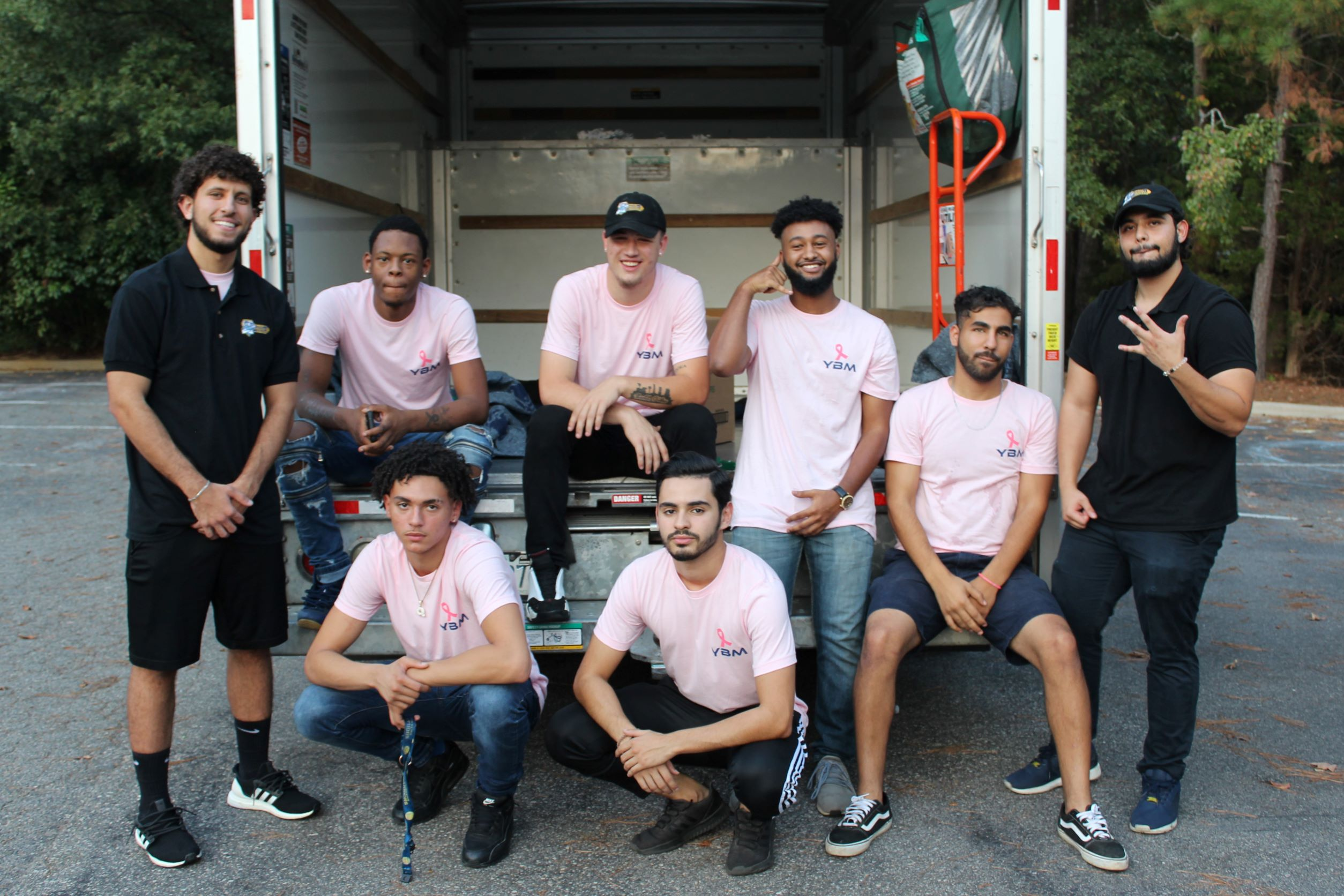 YBM crew members and leaders pose with the breact cancer awareness merch infront of a truck