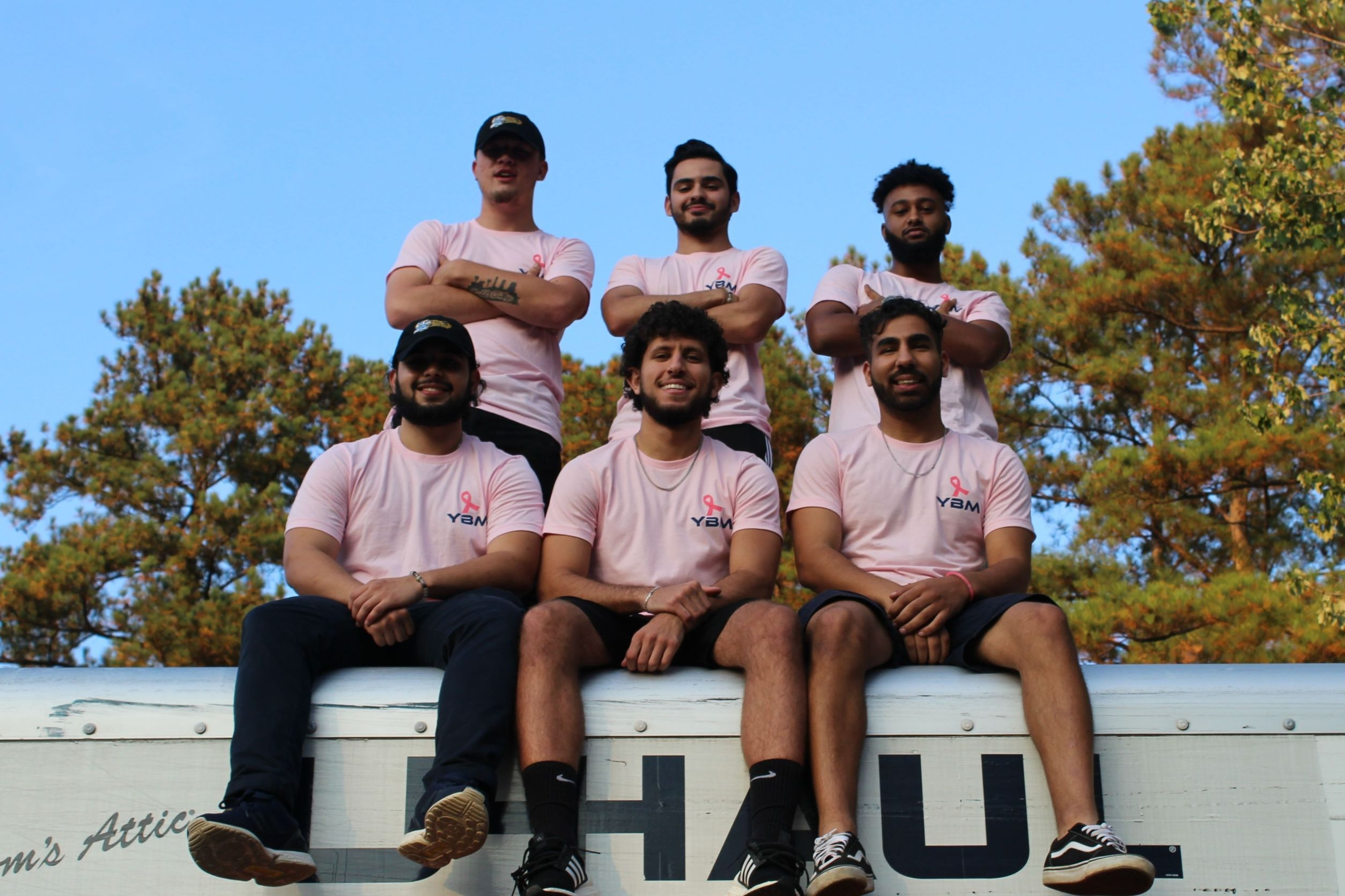 YBM crew members and leaders pose with the breact cancer awareness merch on top of a truck